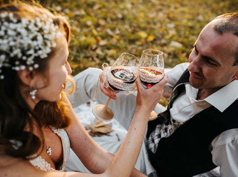 A couple toast each other at their summer wedding