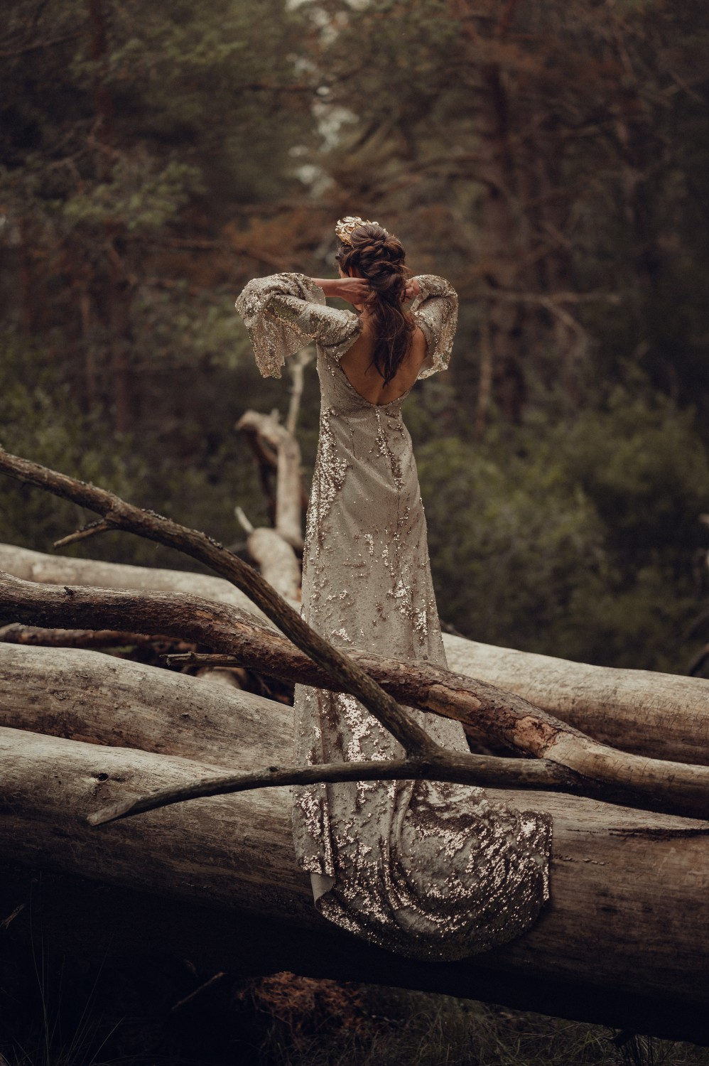 The bride stands on a huge tree at her Highland elopement.
