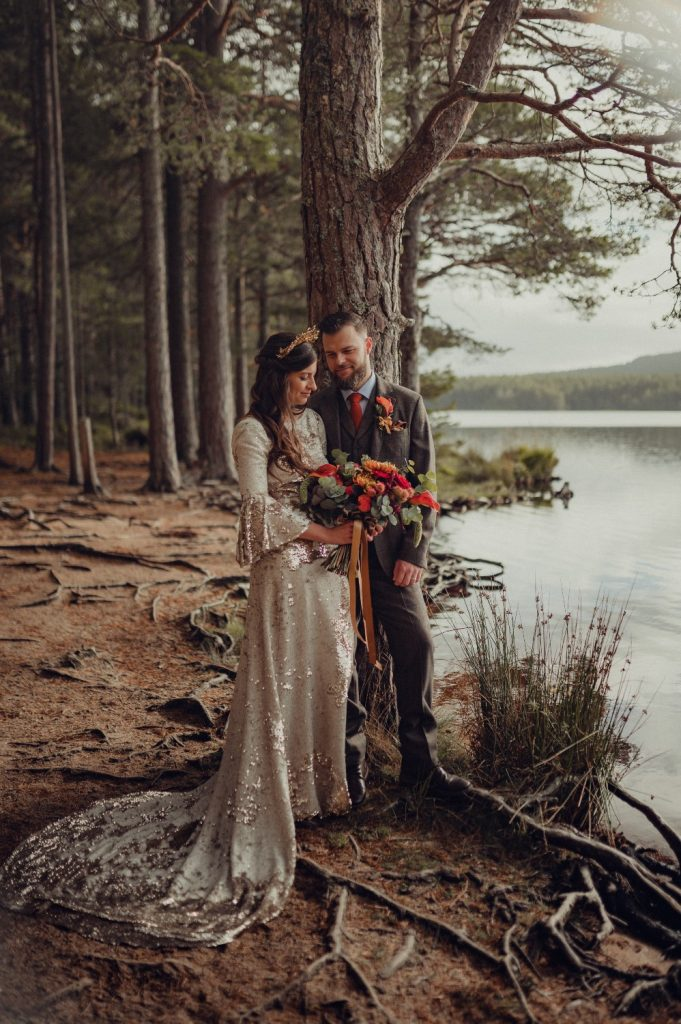 The couple stand by the edge of the loch in the Cairngorms National Park enjoying a quiet moment together at their Highland wedding