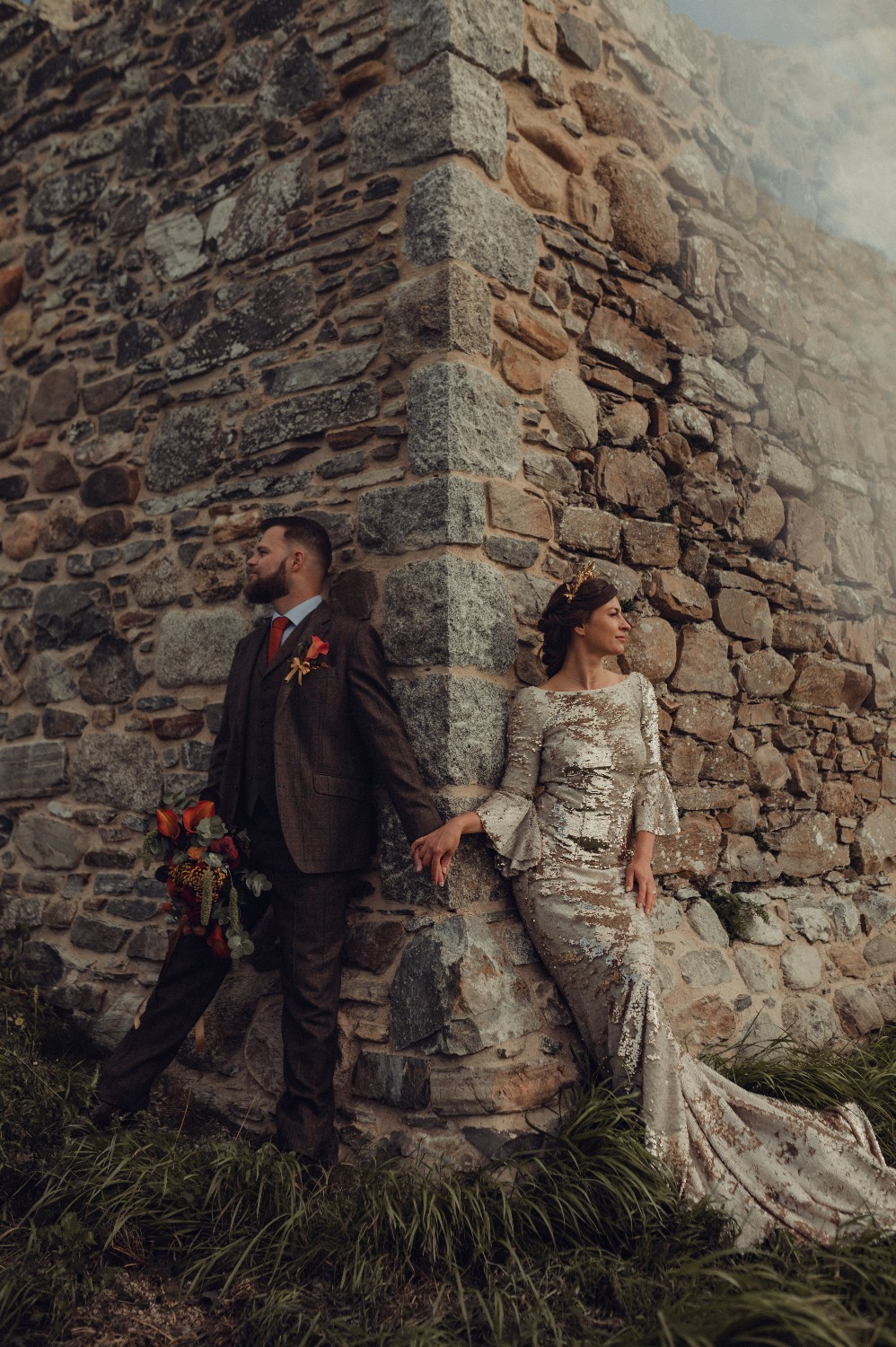 Dramatic, autumnal scene with the bride and groom leaning on the walls of Castle Roy in Nethy Bridge in Scotland